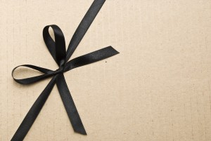 Black satin ribbon and bow on cardboard background